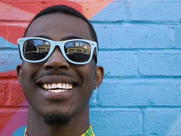 man wearing blue sunglasses in front of colorful wall