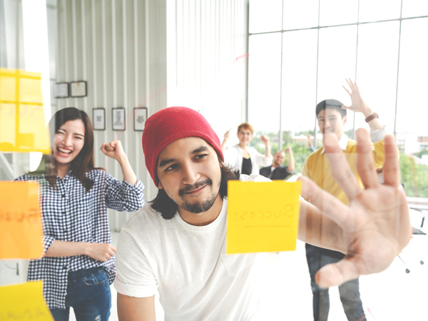 man looking at sticky note posted on glass wall while teammates cheer him on behind him