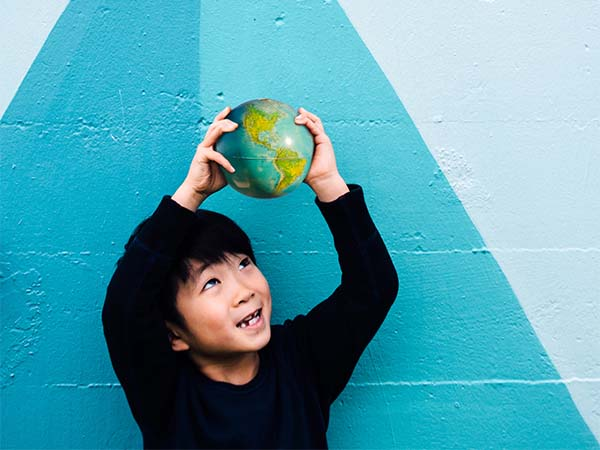Young boy holding up a small ball that looks like earth