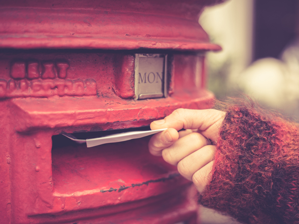 A hand putting direct mail in a mailbox
