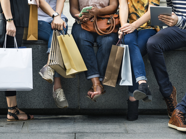 people sitting on a ledge holding shopping bags