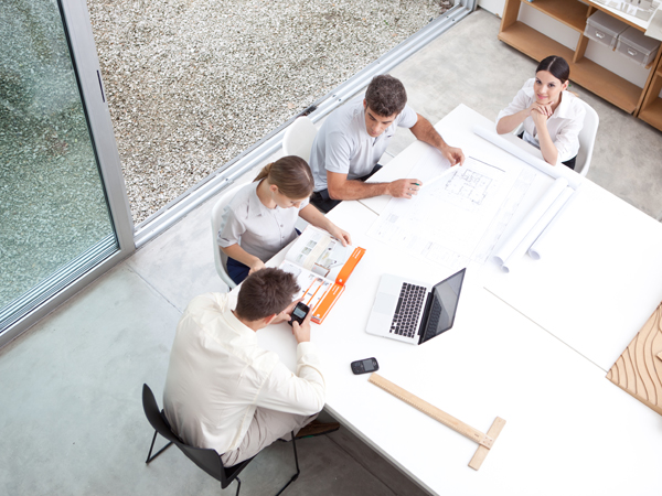 team of people collaborating together at a large desk