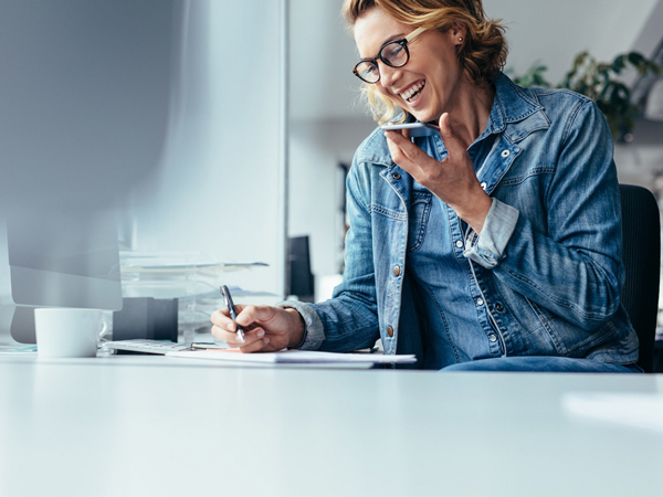 woman smiling in her office, jotting down notes while talking on her cellphone