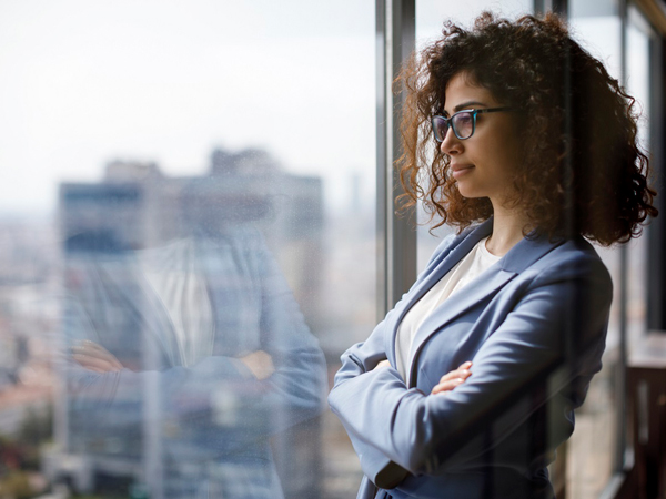 female businesswoman with arms crossed looking out office window