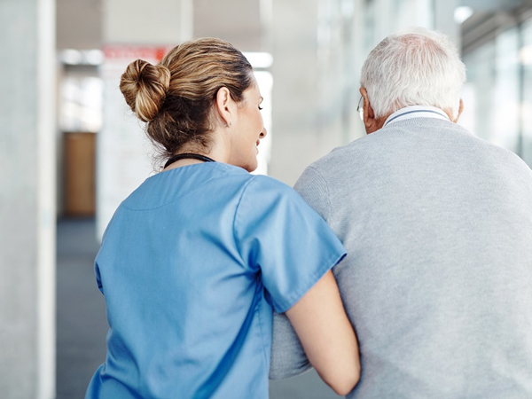 nurse assisting a senior patient with walking