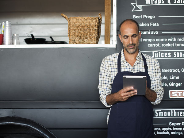 Man holding an ipad standing in front of food truck