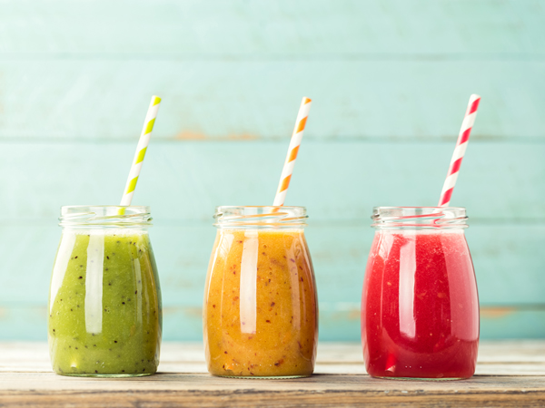 green, yellow, and red smoothies lined up on a table