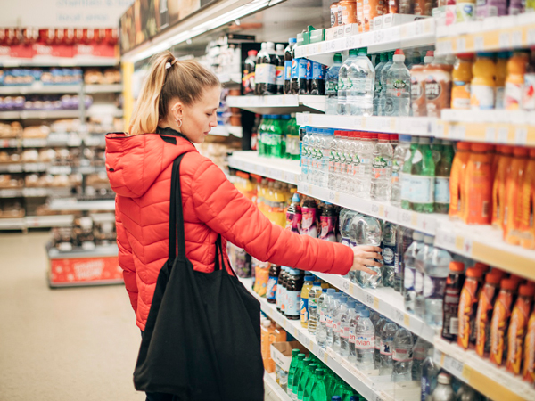 woman in puffy, orange jacket and black bag over her shoulder in an aisle at the grocery store looking at products