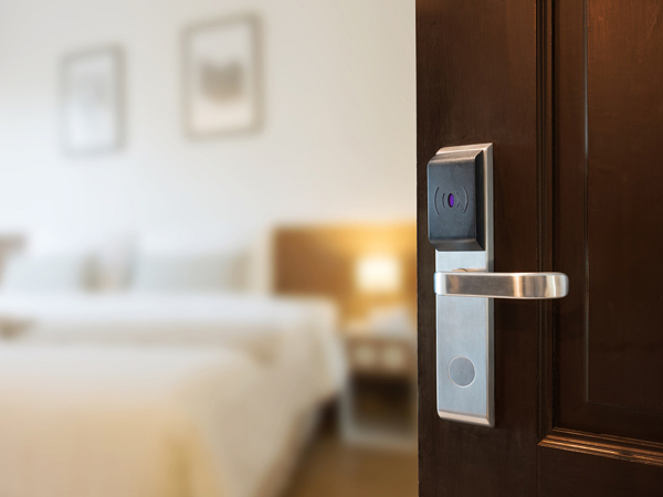 door with hotel room card reader opening to show inside hotel room