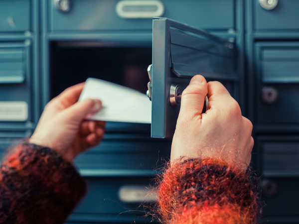 woman pulling direct mail out of mail box