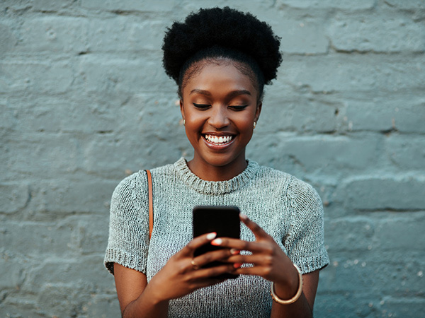 woman smiling while looking at cell phone