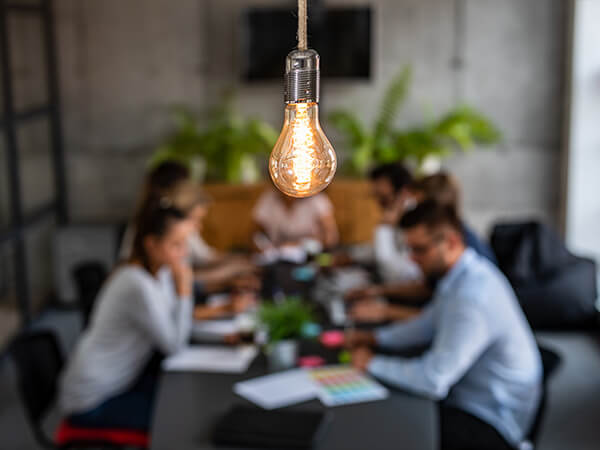 image focused on lightbulb with team at a conference table behind it