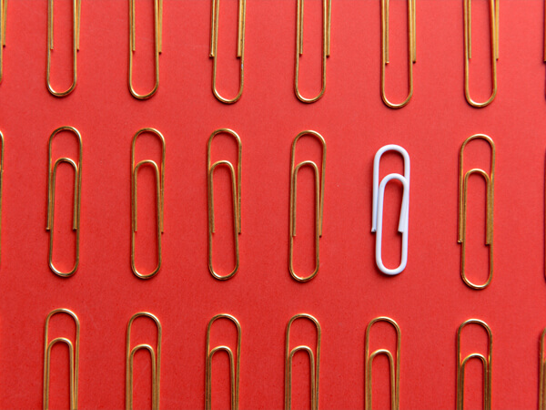 one white paperclip standing out in a sea of gold paperclips
