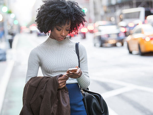 woman in big city looking down at cell phone