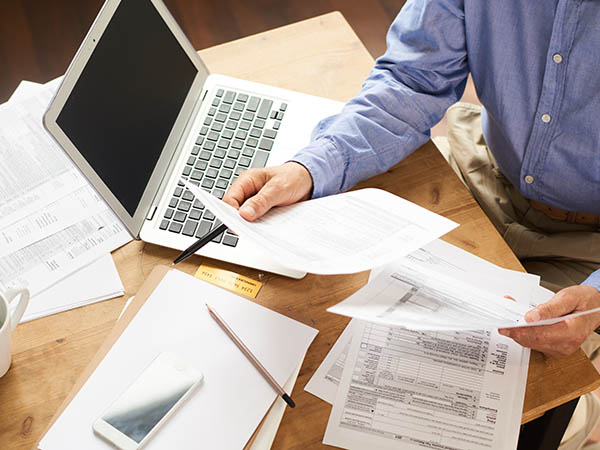 Man filling out Tax forms at desk